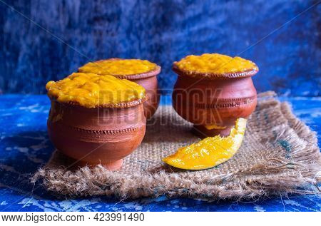 Closeup Of Ripe Mango Pulp Or Aam Ras In Earthen Bowls On Burlap Fabric Isolated On Bluish Backgroun