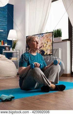 Retired Senior Woman Sitting On Yoga Mat Holding Fitness Dumbbells In Lotus Position During Pilates