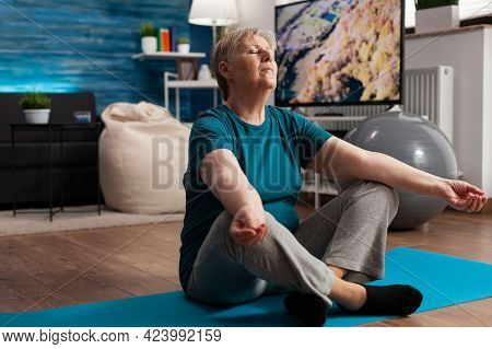 Senior Woman Sitting Comfortable In Lotus Position On Yoga Mat With Closed Eyes Meditating. Peaceful