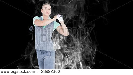 Caucasian female golf player swinging golf club against smoke effect on black background. sports and fitness concept