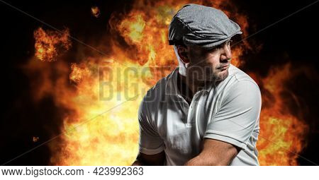 Caucasian male golf player swinging golf club against fire flame effect on black background. sports and fitness concept