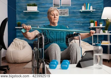 Invalid Senior Woman Exercising Arm Muscle Resistance Using Elastic Band Watching Fitness Video On T