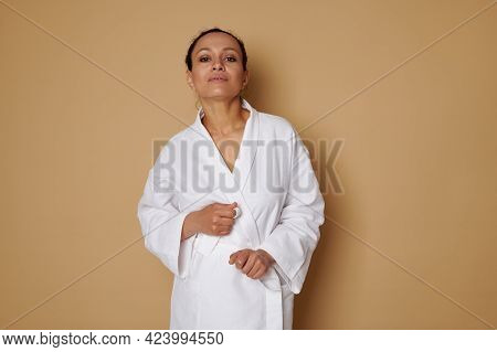 Beautiful African American Woman In White Waffle Bathrobe Posing Over Beige Background With Space. S