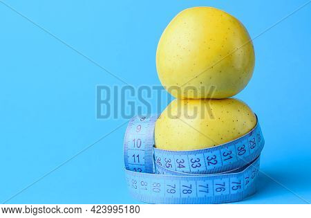 Two Yellow Apples Wrapped In A Centimeter Tape. Healthy Food, Calorie Content. Fitness, Diet, Weight
