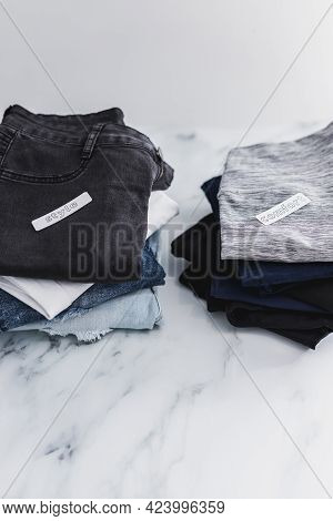 Piles Of Jeans And Pants Being Sorted Into Style Vs Comfort Categories, Decluttering And Prioritizin