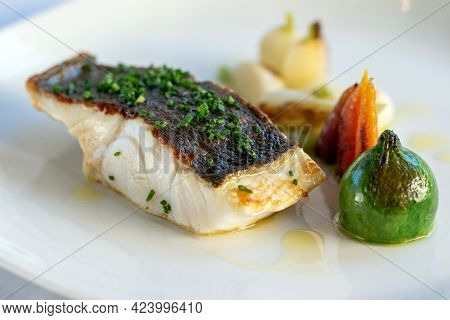 Close Up Gourmet Delicacy Of Fresh Roasted Sea Bass Fillet With Eco Vegetable Garnish.