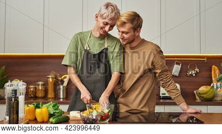 Homosexual Gay Couple Helping Each Other While Preparing Food Side By Side In Kitchen, Widescreen. C