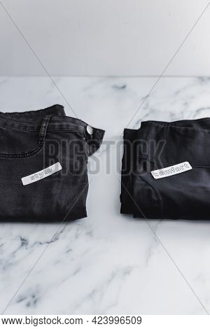 Jeans And Yoga Pants Being Sorted Into Style Vs Comfort Categories, Decluttering And Prioritizing Lo