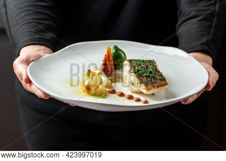 Close Up Front View Of Waiter Holding Gourmet Dish Of Roasted Fish Fillet With Eco Vegetables. White