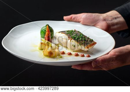 Close Up Side View Of Waiter Serving Dish With Roasted Sea Bass And Eco Vegetables. White Plate With