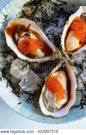 Vertical Top View Of Fresh Oysters With Orange Caviar And Reddish Ponzu Sauce Served On Crushed Ice.