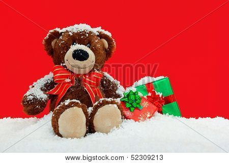 A handmade teddy bear sitting in the snow with gift wrapped Christmas presents against a red background.