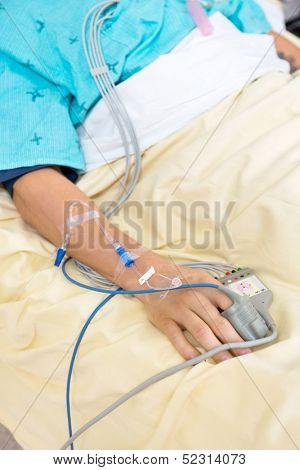 Pulse oximeter attached to male patient's finger in hospital
