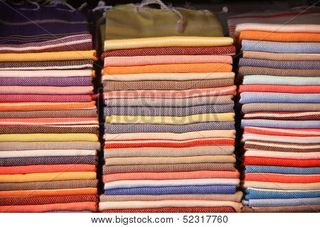 Colorful 100% pure cotton shawls folded and stacked on a shelf. poster