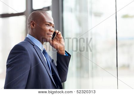 handsome african american businessman talking on mobile phone in modern office