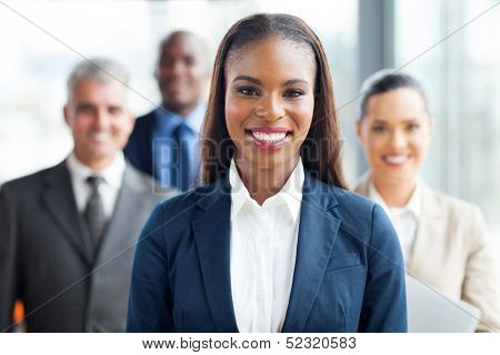 pretty african american businesswoman standing in front of co-workers