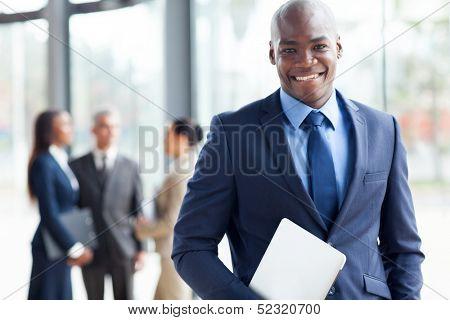 gut aussehend afroamerikanischer Geschäftsmann mit Laptop-Computer im Büro