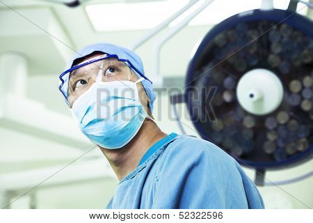 Low angle view of surgeon wearing a surgical mask and glasses in the operating room