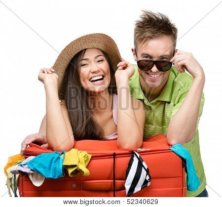 Couple packs up suitcase with clothing for trip, isolated on white. Concept of romantic vacations and lovely honeymoon