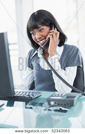 Smiling stylish businesswoman on the phone while working on computer in bright office