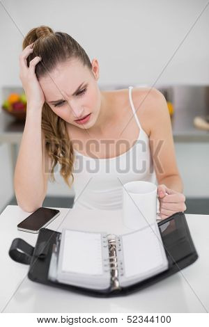 Stressed young woman holding a mug looking at open diary in the kitchen at home