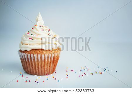 Vanilla cup cake with white icing and candies on top