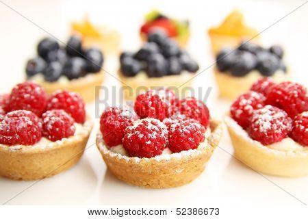 Assortment of fruity tarts on white background