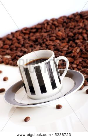 Coffee Beans Behind A Cup Of Black Coffee