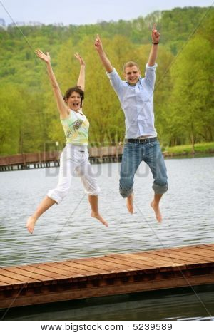 Couple Is Jumping In Front Of A Lake