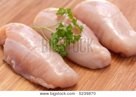 Chicken Breast Fillets On Wooden Chopping Board Background.