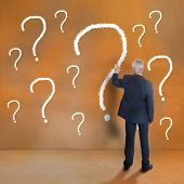 Mature businessman touching question mark on beige wall poster