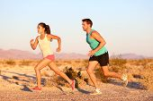 Cross-country trail running people at sunset. Runner couple exercising outside as part of healthy lifestyle. Multiracial runners couple, Asian woman, Caucasian man working out together. poster
