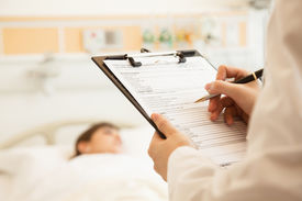 Close up of doctor writing on a medical chart with patient lying in a hospital bed