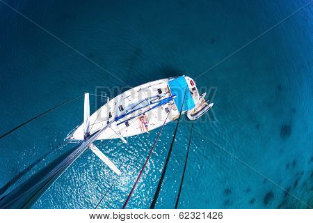 Young couple relaxing on board of the sail boat anchored in shallow tropical bay