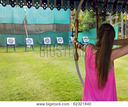 Archer young woman pulls the bowstring and arrow aiming at a target poster