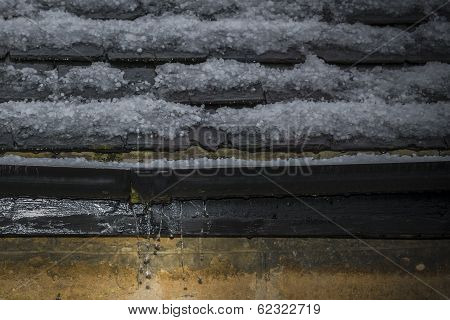 Gutter leaking water after a hailstorm in spring time