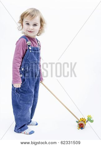 Preschooler With Toy Standing In Light Background
