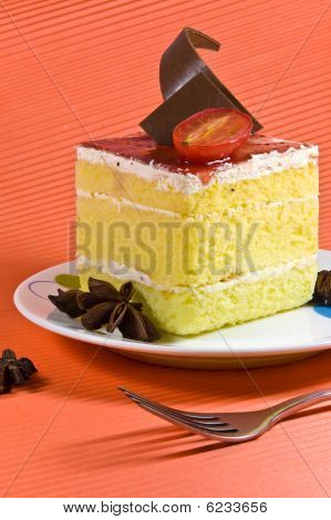 Tasty And Colorful Yellow Cake With White Cream Layer And Chocolate Decorations.