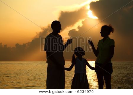 three silhouettes against glossing sea. Daughter between parents.
