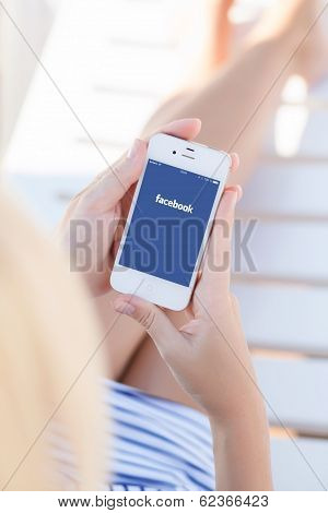 Girl In A Bathing Suit Holding A White Iphone With Facebook On A Screen