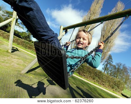 Carefree child on a swing in a park on summer day