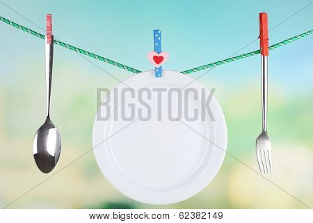 Tableware dried on rope on natural background