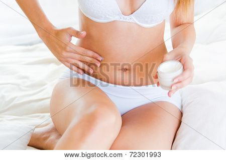 Young Woman Applying Skin Moisturizer Abdomen. Isolated On White.