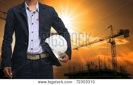 engineer man standing with white safety helmet against beautiful dusky sky with building construction site use for engineering and construction industrial business poster