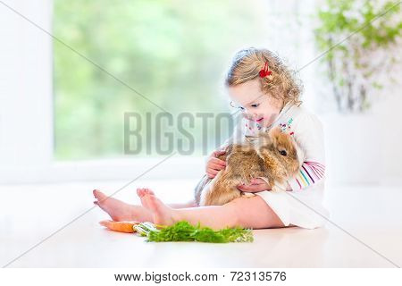 Adorable toddler girl with beautiful curly hair wearing a white dress playing with a real bunny in a sunny living room with a big garden view window sitting on the floor poster