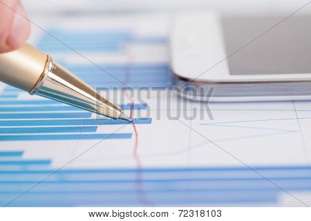 Businessman Analyzing Bargraph At Desk