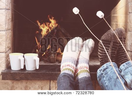 Feet Of The Couple Warming At A Fireplace
