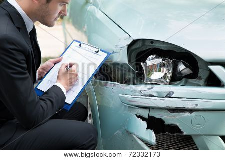 Side view of writing on clipboard while insurance agent examining car after accident poster