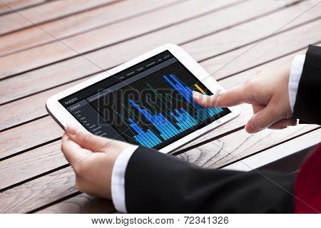Businesswoman Analyzing Bargraphs On Digital Tablet