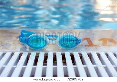 Close up shot of a blue goggles by the swimming pool poster